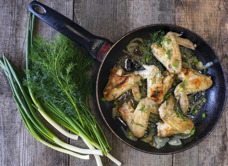Fried chicken wings in frying pan with herbs and spring onions on wooden table