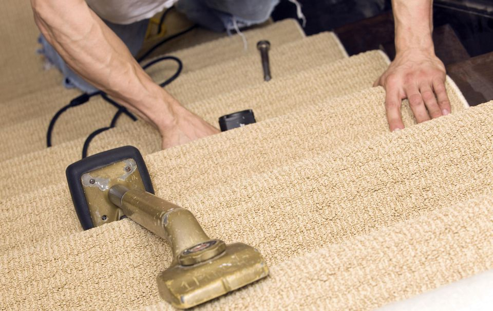 Installer stapling stair carpet with knee kicker