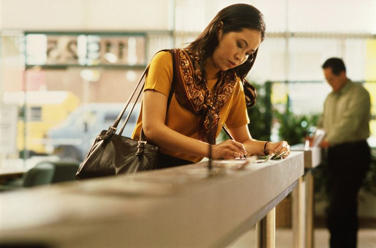 Woman in bank filling out banking slip on counter