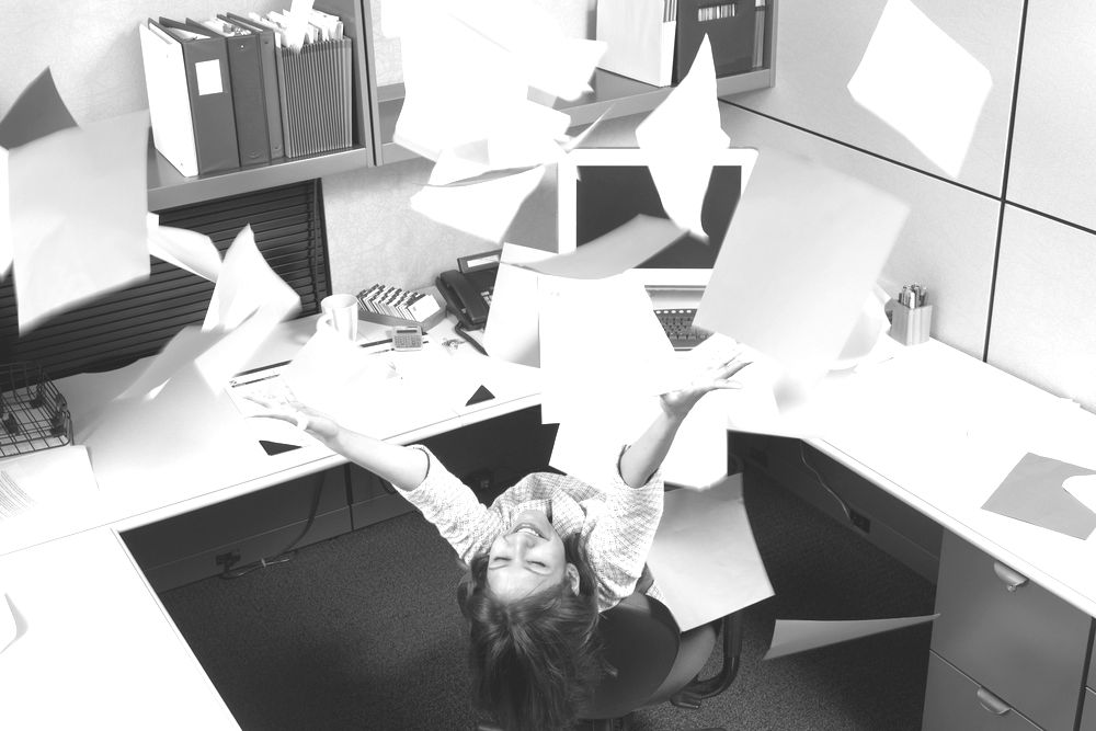 Ecstatic businesswoman throwing office papers