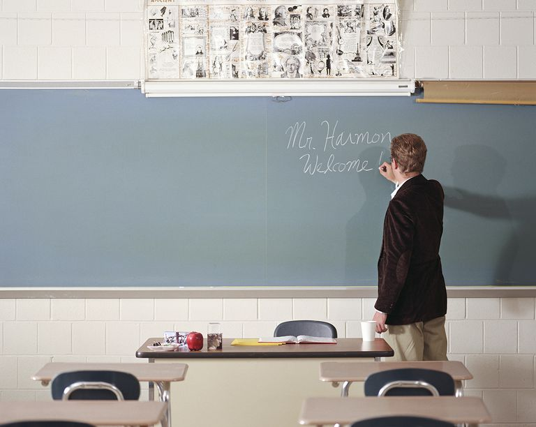 Teacher writing name on blackboard on first day of class, rear view.