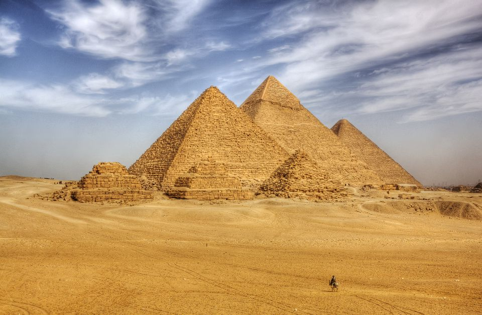 A lone traveler approaches the Pyramids of Giza
