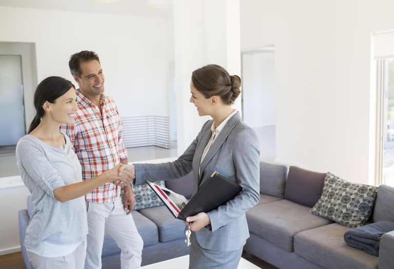 Realtor and couple handshaking in living room