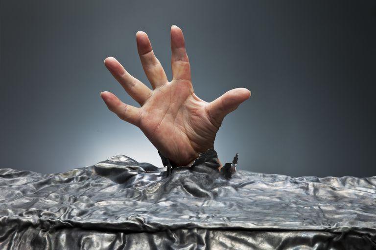 A Hand Reaching through Metal