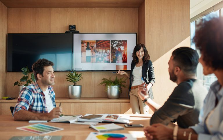 Group of creative designers discussing new marketing ideas together in boardroom.
