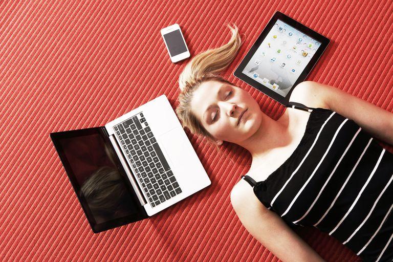 woman laying beside technology