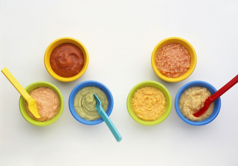 Homemade meat, vegetable, cheese and fruit purees in brightly coloured bowls with spoons