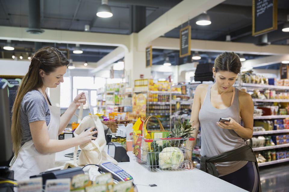 Woman using cell phone at grocery store checkout