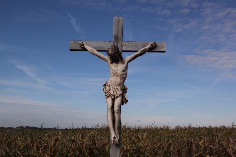 Low Angle View Of Jesus Christ Statue On Cross At Field Against Sky