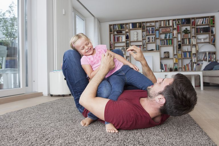 Father tickling young daughter.