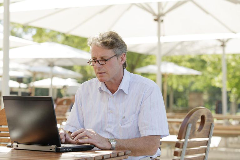 Man busy on laptop in garden restaurant
