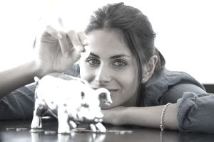 Woman putting coin into piggy bank