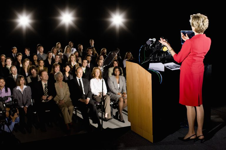 Woman at podium facing audience.
