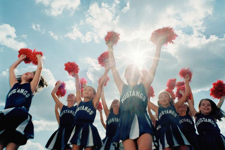 Group of cheerleaders (8-10) jumping, outdoors