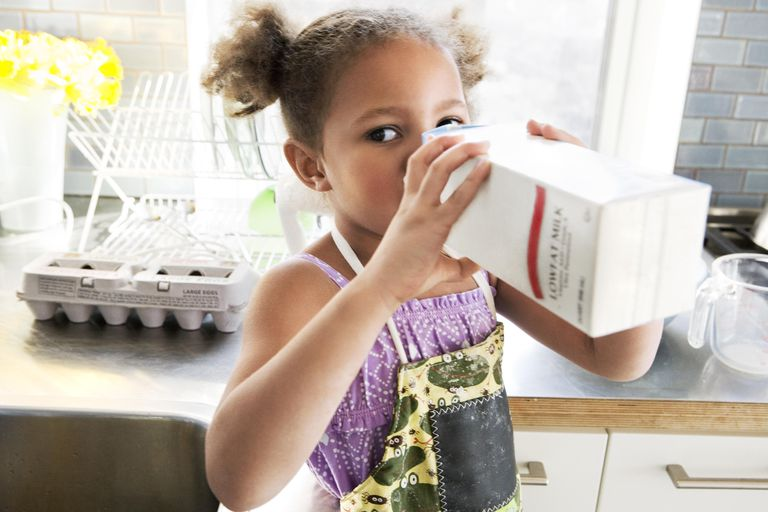 Young child drinking milk out of carton
