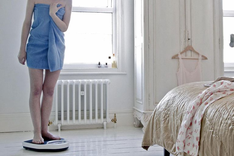 Woman weighing herself at home