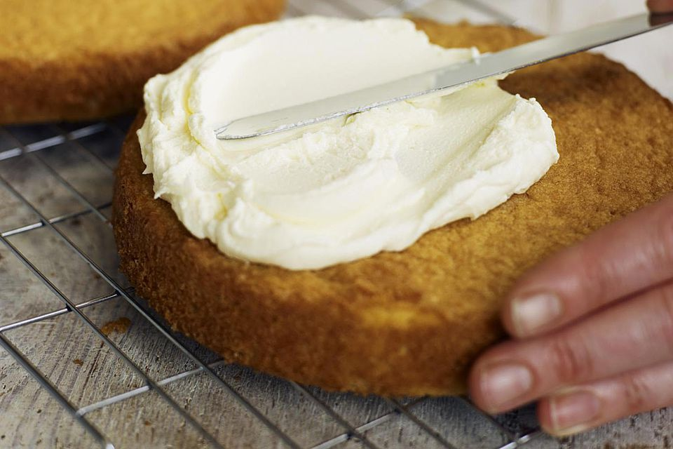 Spreading butter icing on Victoria sponge cake