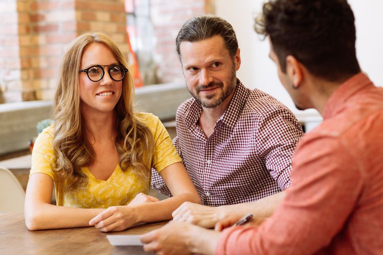 couple talking to man across table