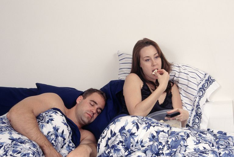 Couple in bed w/ woman eating popcorn