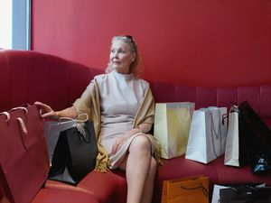 Senior Woman Sitting Between Shopping Bags on Red Couch
