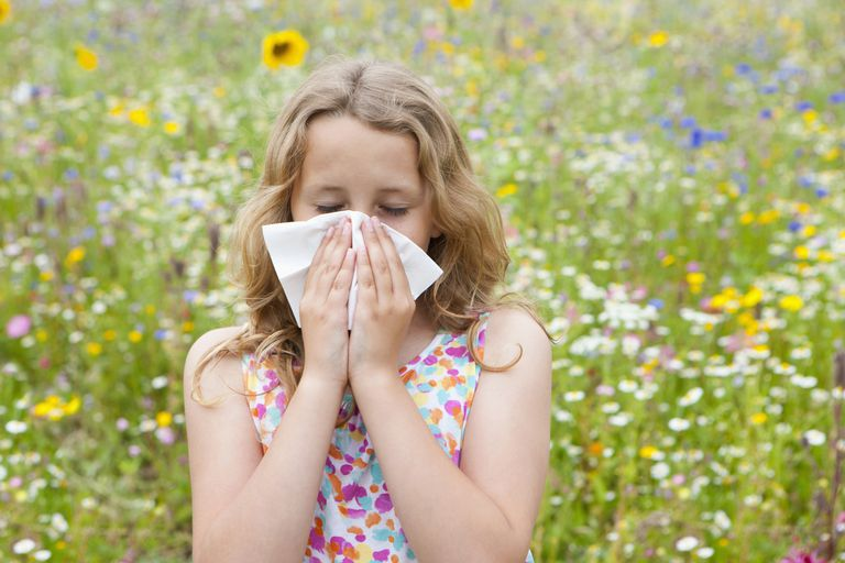 Girl in field of flowers blowing nose
