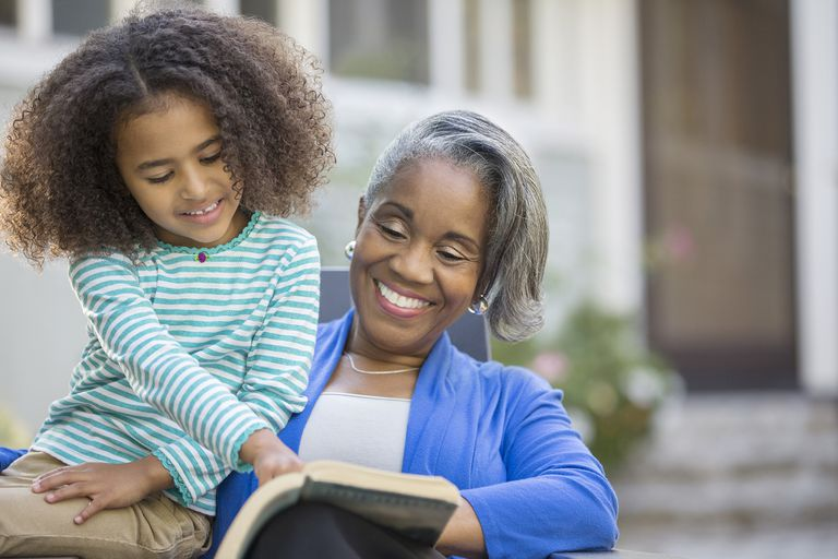 Girl reading book with grandmother