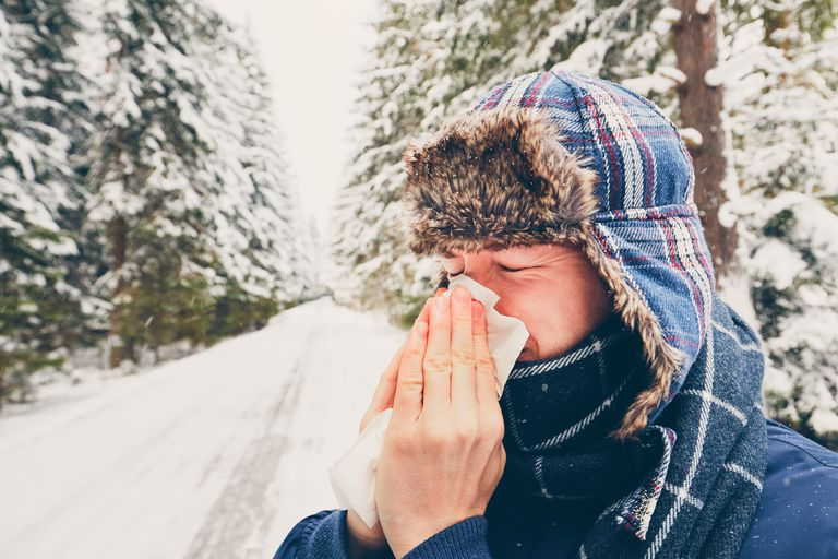 man blowing nose in snow outside