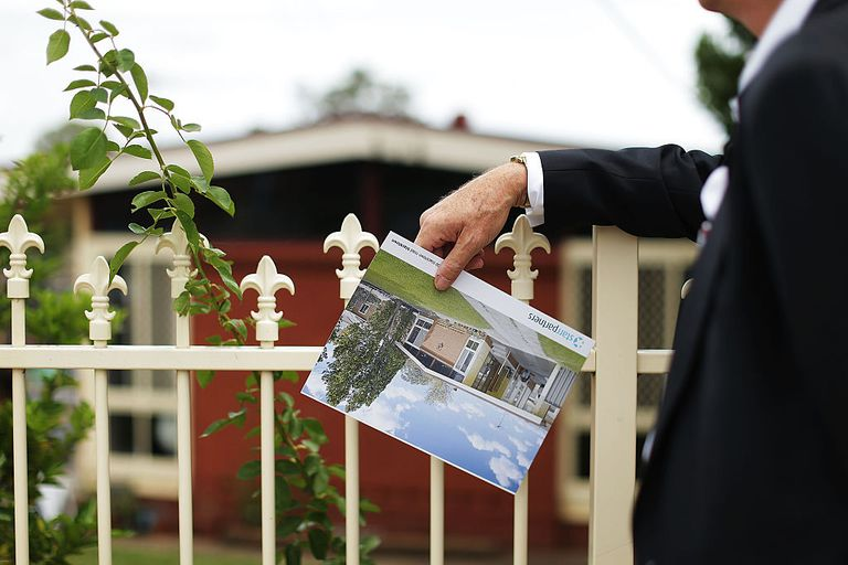 Man in suit loking at house for sale
