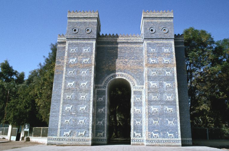 tall, blue structure, two towers connecting one arch, with white four-legged animals dotting the facade