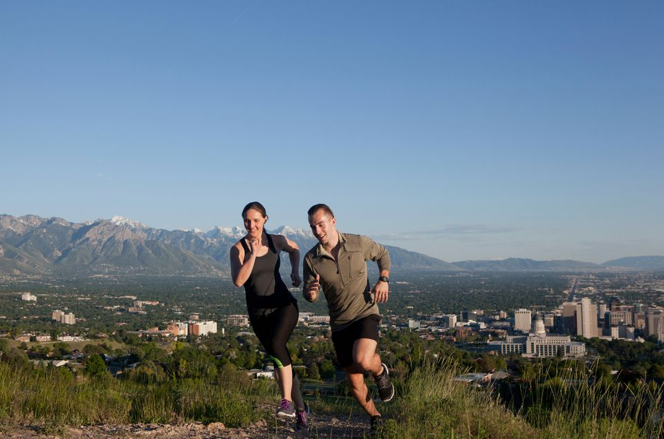 Young female and male runners racing along track above city in valley