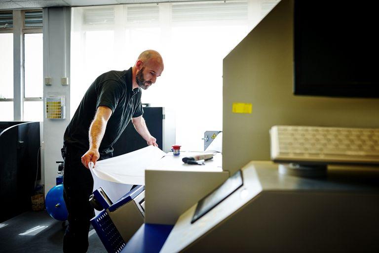 Man standing working on offset printing machine ch