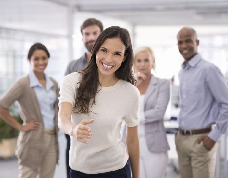 Joyful woman with her team welcome you to her workplace with joy