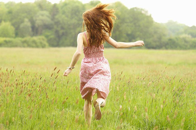 Woman running through meadow.