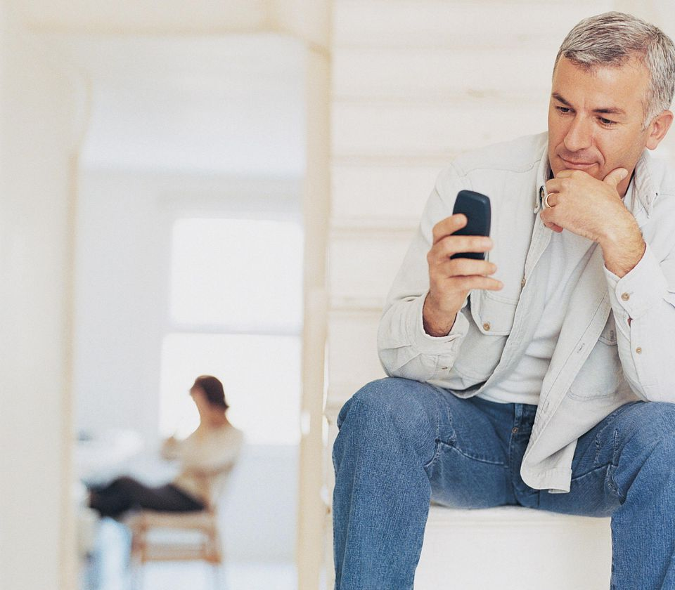 Man Checking Text Messages with a Woman Seated in Background
