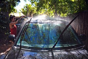 Young woman washing her new car