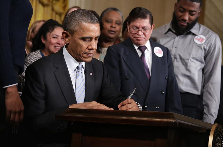 U.S. President Barack Obama signs an executive order to raise the minimum wage for federal contractors from $7.25 to $10.10