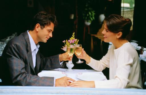 Couple with glass of wine holding hands across table