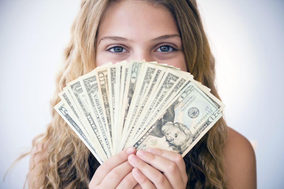 Girl holding US money in a fan
