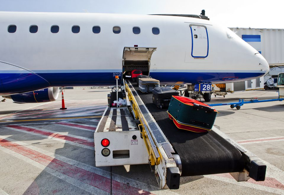 Luggage on conveyor belt by airplane cargo hold
