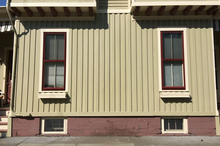 vertical siding, two elongated windows over two cellar windows and below two bay windows