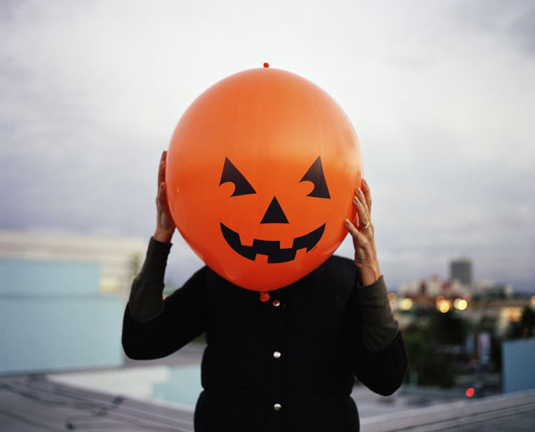 Picture of a woman holding a jack o' lantern balloon in front of her face