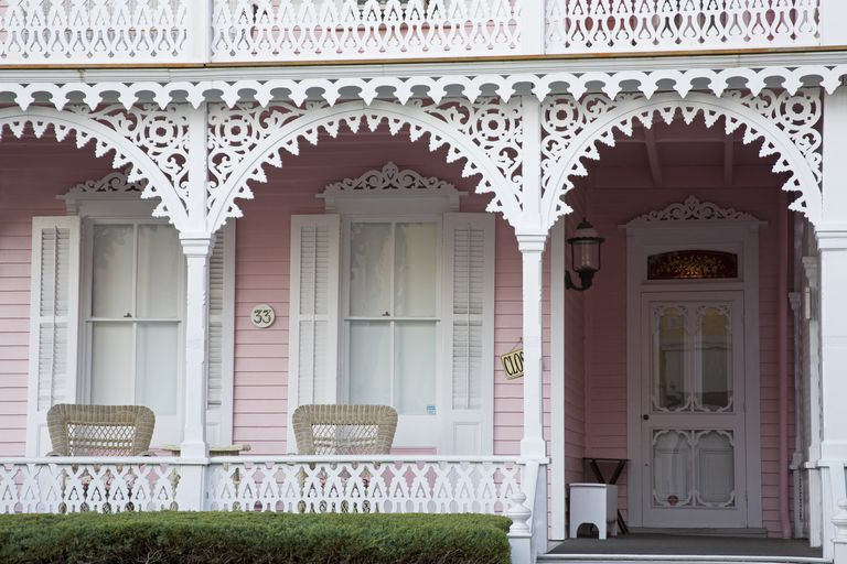 Ornate porch detail in white, white shutters, pink house siding