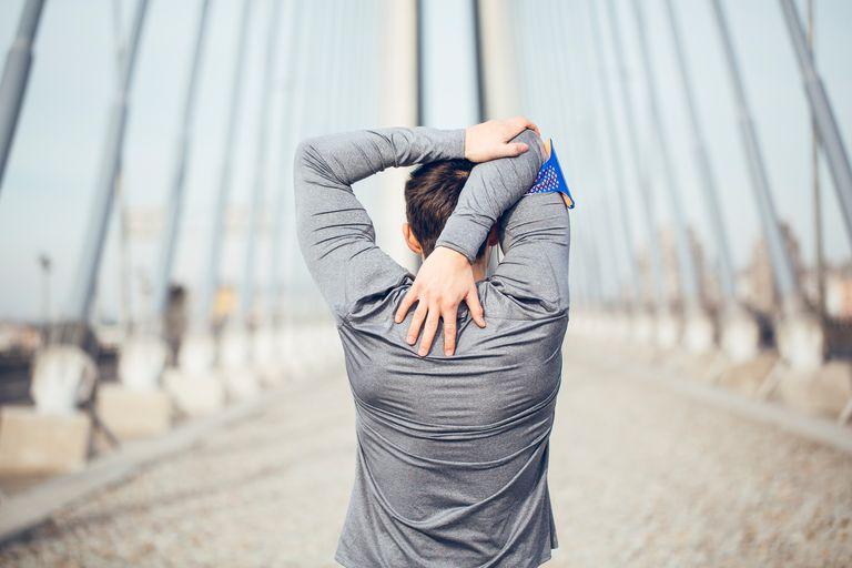 Man stretching on bridge