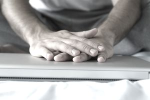Hands folded on top of a closed laptop