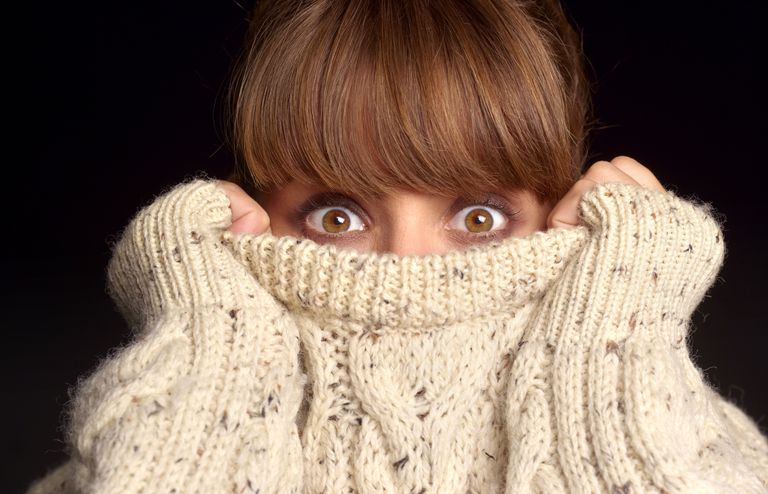 scared woman with sweater pulled over lower face