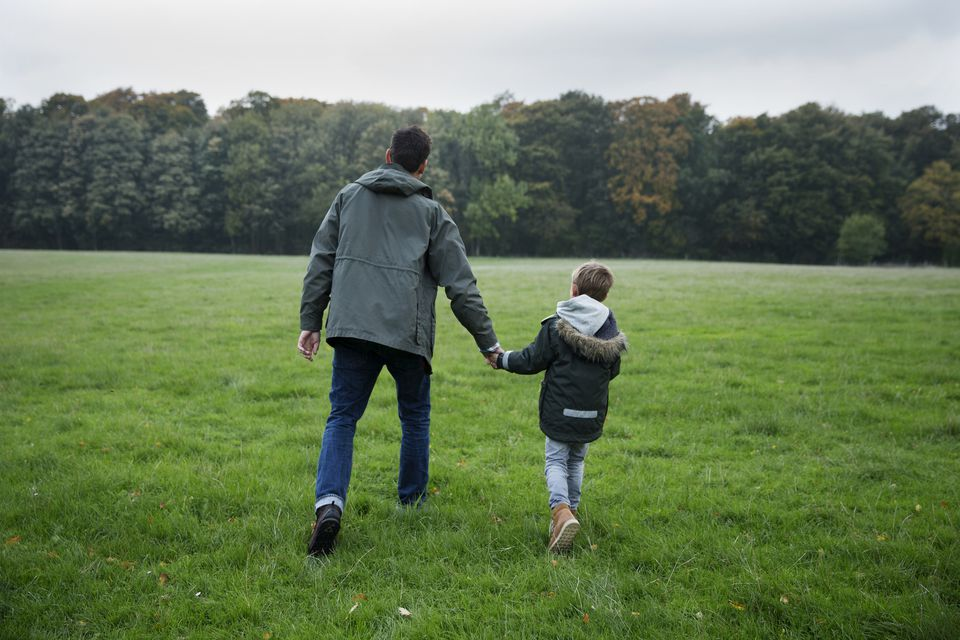 Father and son walking in nature, holding hands