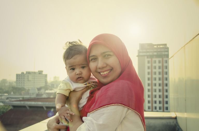A woman wearing a hijab holds a baby
