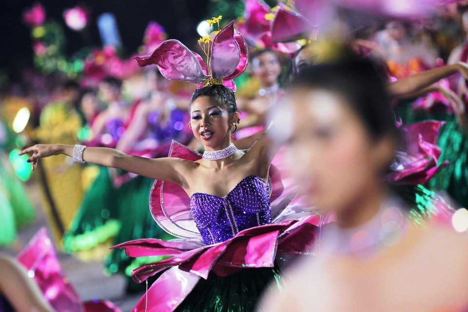 Chingay performers dance down the street in Singapore.