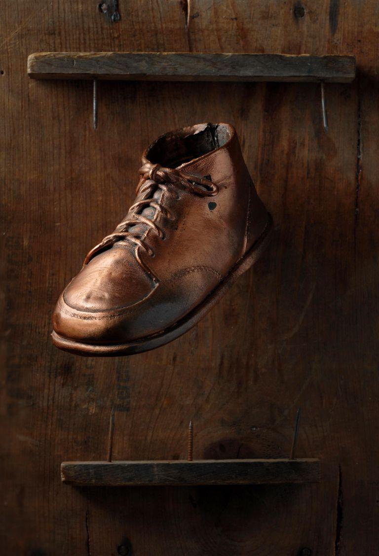 Bronzed Vintage Baby Shoe Set Against Wood