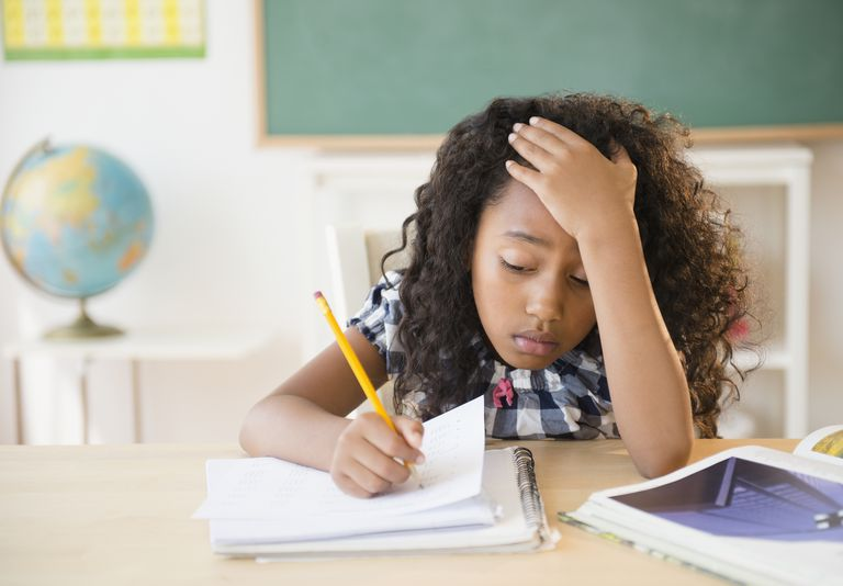 Frustrated mixed race student working in classroom
